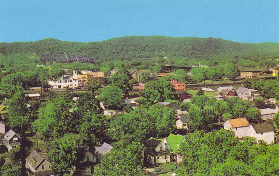 1965 View of Kenova, West Virginia City Hall and N&W Railroad Bridge on left.  Union Depot is at right.  More coal has passed over this point than any place in the world!  Hills of Ohio in the background. Issued by Griffith & Feil Drugs, Kenova WV