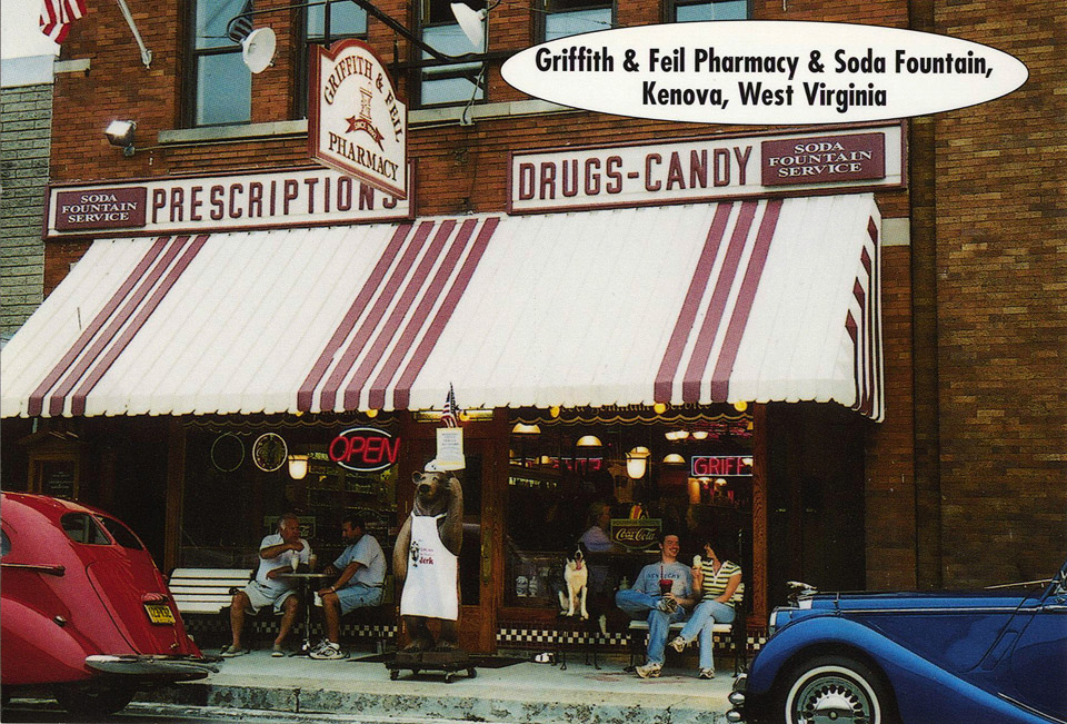 Griffit & Feil Pharmacy & Soda Fountain, Kenova, West Virginia  Simp, the Griffith & Feil Pharmacy bear, greets visitors at the old fashioned soda fountain and drug store in Kenova, West Virginia, just off Exit 1 of I-64.  Opened in 1892, the pharmacy remains the oldest continuous business in Kenova, serving delicious food and wonderful treats for breakfast, lunch, and dinner.  The tin ceiling, oak floors, antique fixtures, and Wurlitzer juke box recreate the nostalgic experience of an authentic drug store soda fountain. G&F card #21